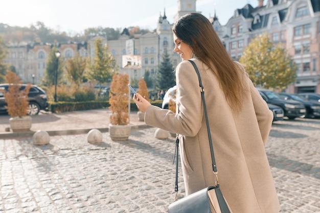 Souriante Jeune Femme Avec Un Téléphone Portable Marchant Photo Premium