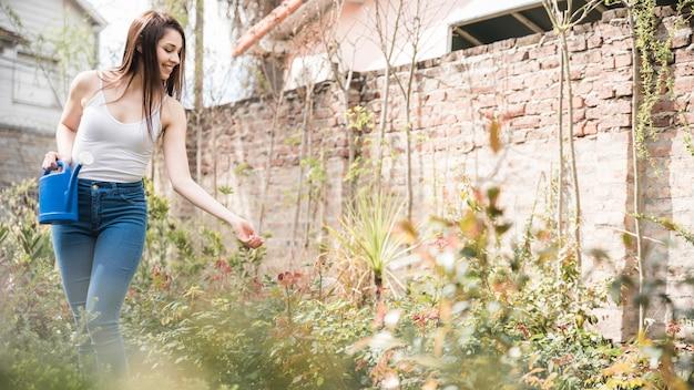 Souriante jeune femme tenant un arrosoir à la main en prenant soin des plantes dans le jardin Photo gratuit