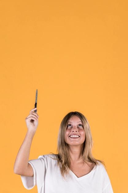 Souriante jeune femme tenant un crayon levant sur fond jaune Photo gratuit