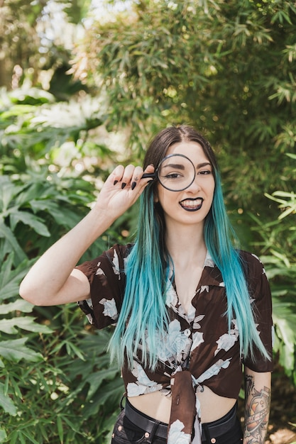 Souriante jeune femme tenant une loupe sur ses yeux Photo gratuit