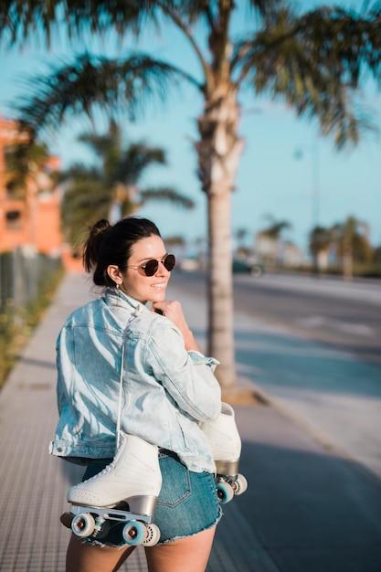 Souriante jeune femme tenant des patins à roulettes sur l'épaule, regardant par-dessus l'épaule Photo gratuit
