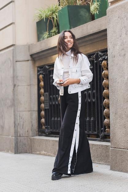 Souriante jeune femme tenant un téléphone portable à la main, debout sur le trottoir Photo gratuit