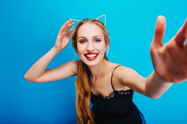 Souriante Jolie Blonde Aux Yeux Bleus Posant, Prenant Selfie, Profitant De La Fête. Porter Une Robe Noire Et Un Bandeau Avec Des Oreilles De Chat. Photo gratuit