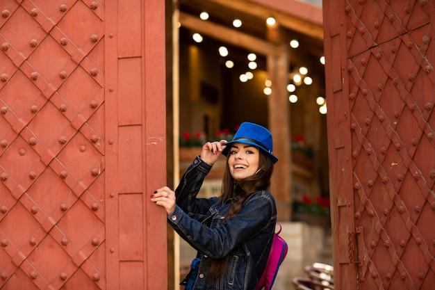Souriante jolie fille au chapeau bleu près du vieil immeuble avec des portes rouges antiques. modèle féminin pose Photo Premium