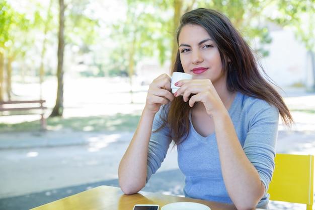 Souriante jolie jeune femme buvant du café à la table du café dans le parc Photo gratuit