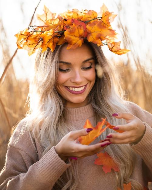 Souriante jolie jeune femme portant des feuilles d'érable diadème jouant avec les feuilles de l'automne Photo gratuit