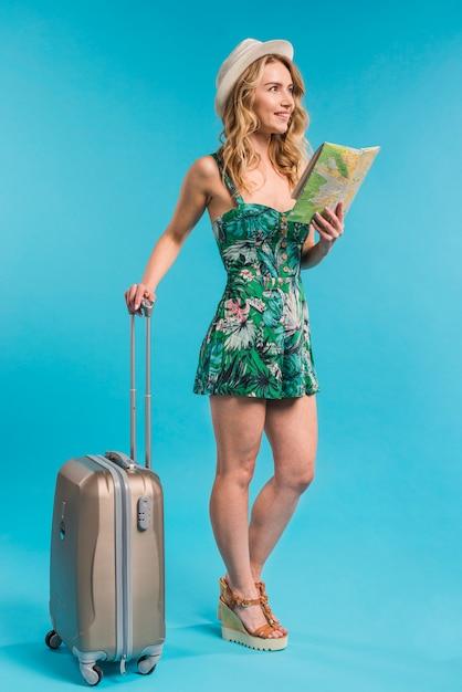 Souriante séduisante jeune femme au chapeau tenant la carte et la valise Photo gratuit