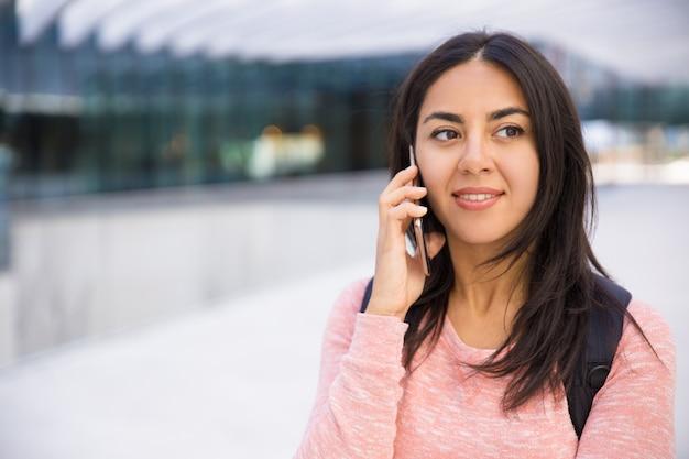 Souriante séduisante jeune femme communiquant sur un téléphone mobile Photo gratuit
