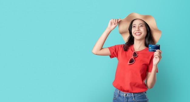 Souriez avec bonheur femme asiatique tenant la carte de crédit et impatient sur fond bleu avec espace de copie. Photo Premium