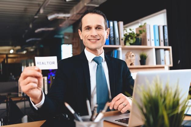 Sourire agent immobilier assis au bureau avec carte de visite. Photo Premium
