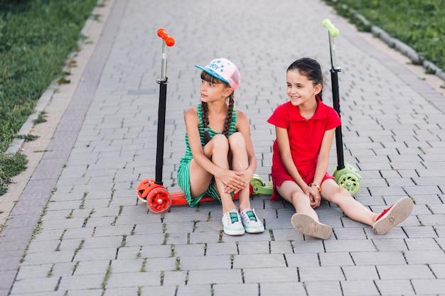 Sourire des amies assis sur leurs trottinettes dans le parc Photo gratuit