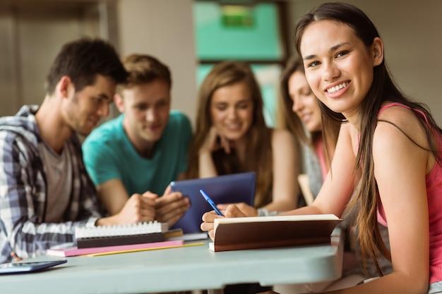 Sourire des amis assis à étudier et à l'aide de tablet pc Photo Premium