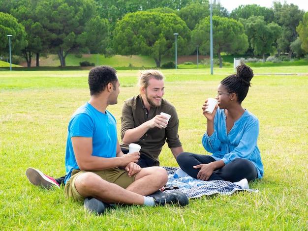 Sourire amis boire des gobelets en papier dans le parc Photo gratuit