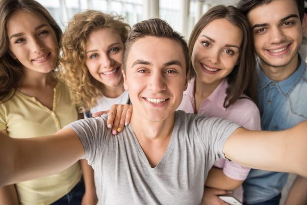 Sourire des amis prenant selfie avec téléphone au collège. Photo Premium