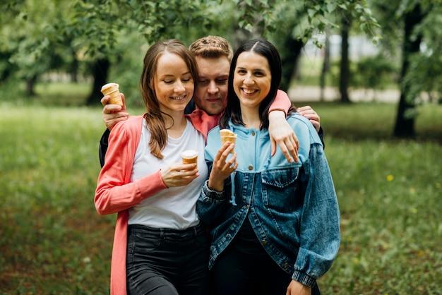 Sourire des amis traîner dans le parc avec de la glace Photo gratuit