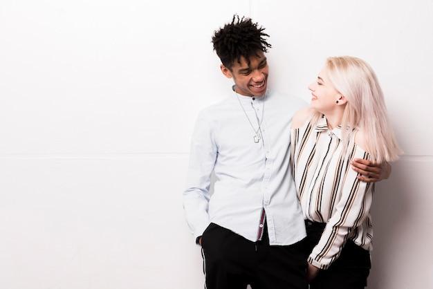 Sourire amoureux couple interracial embrassant debout contre le mur blanc Photo gratuit