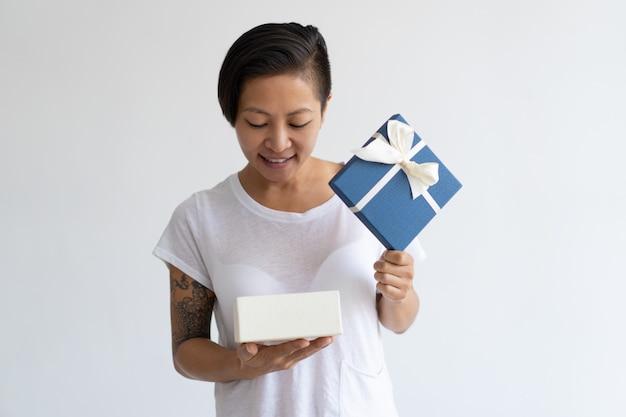 Sourire asiatique femme regardant dans une boîte cadeau ouverte Photo gratuit