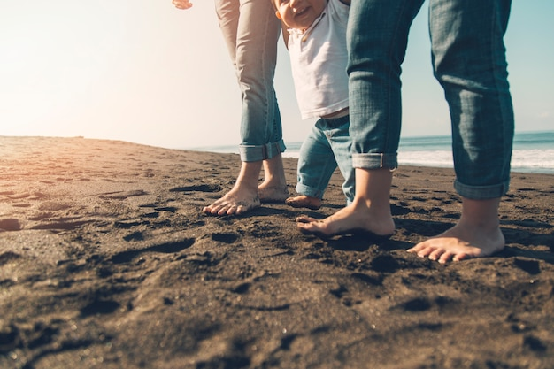 Sourire Bébé Fait Ses Premiers Pas Avec Ses Parents Sur La Plage Ensoleillée Photo gratuit