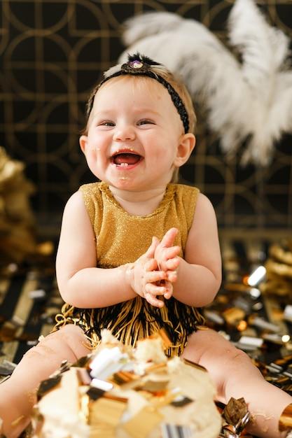 Sourire bébé fille fête son premier anniversaire, manger un gâteau Photo gratuit