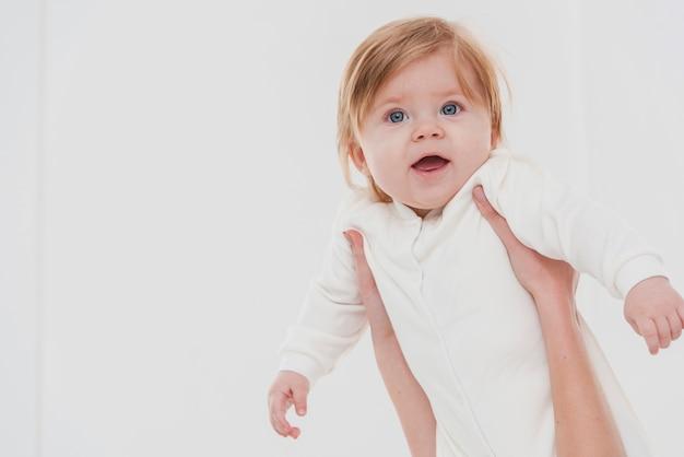 Sourire bébé tenu pour pose Photo gratuit