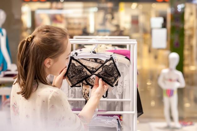 Sourire Belle Brune En Choisissant Le Bikini En Se Tenant Debout Dans La Boutique Photo Premium
