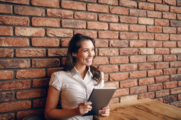 Sourire Brunette Caucasien Mignon Assis Dans Un Café Et à L'aide De Tablette. En Arrière-plan Mur De Briques. Photo Premium
