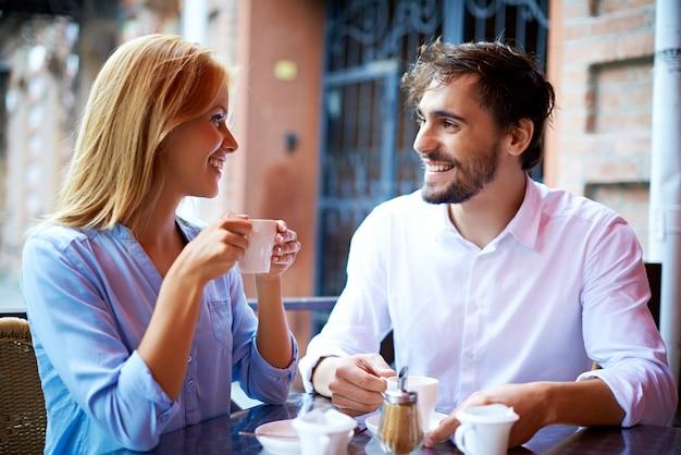 Sourire Café Couple Potable Et En Regardant Les Uns Les Autres Photo gratuit