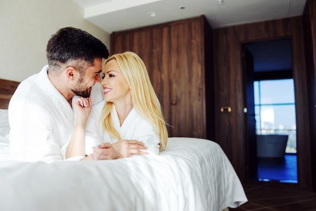 Sourire Couple D'âge Moyen Amoureux Allongé Sur Le Ventre Dans Son Lit Et Câlins. Ils Fêtent Leur Anniversaire à L'hôtel. Photo Premium