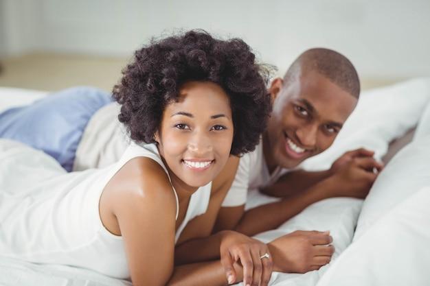 Sourire couple allongé sur le lit en regardant la caméra Photo Premium