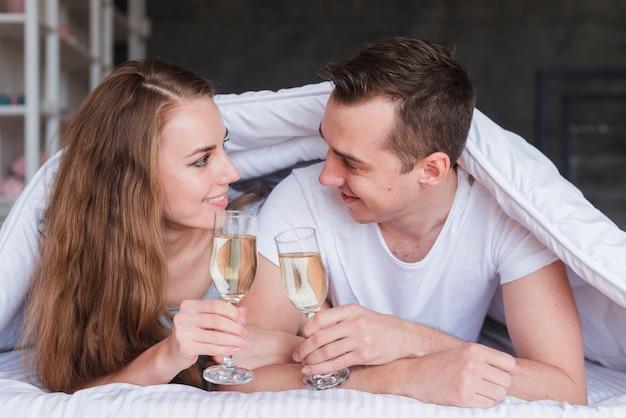 Sourire couple allongé sur le lit sous la couette avec des verres de boisson Photo gratuit