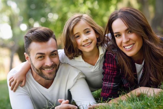 Sourire Couple Allongé Sur La Pelouse Avec Leur Fille Photo gratuit