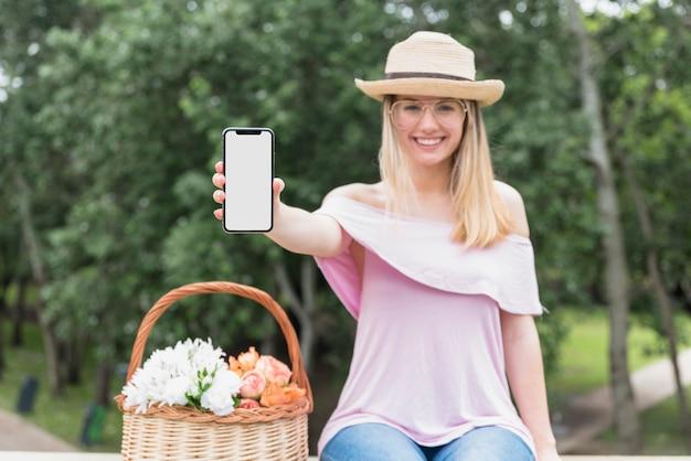 Sourire dame à lunettes et chapeau montrant téléphone mobile Photo gratuit