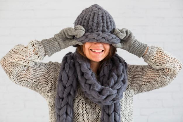 Sourire dame en mitaines, écharpe et bonnet sur les yeux Photo gratuit