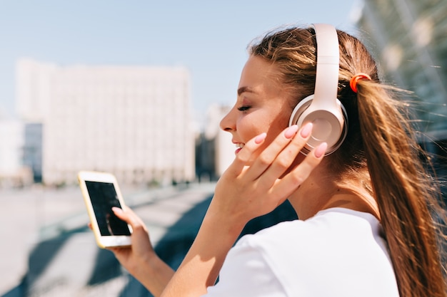 Sourire Et Danser Jeune Femme Tenant Un Smartphone Et écouter De La Musique Dans Les écouteurs Photo gratuit