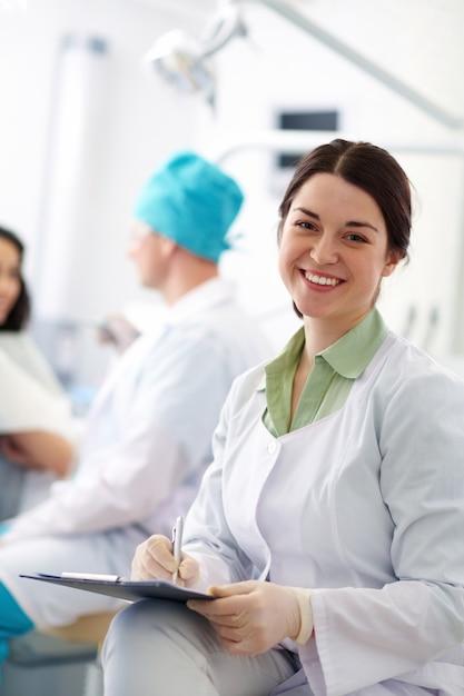 Sourire dentiste à la clinique Photo gratuit