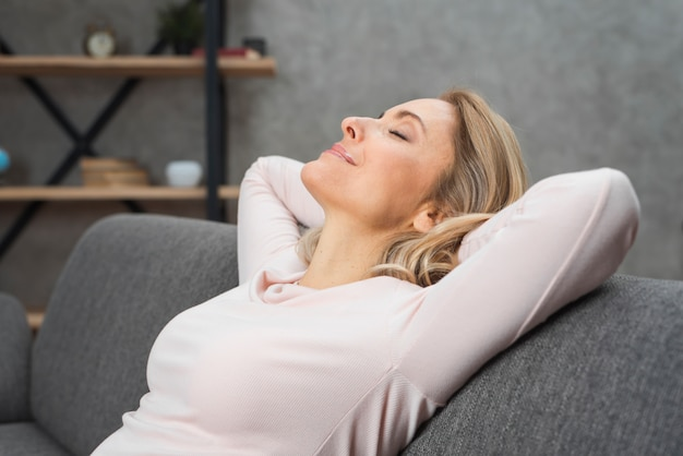 Sourire détendue jeune femme se penchant la tête sur un canapé Photo gratuit