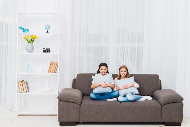 Sourire deux filles assis sur un canapé avec un coussin dans le salon moderne Photo gratuit