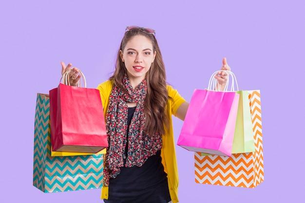 Sourire élégante femme montrant le sac en papier coloré Photo gratuit
