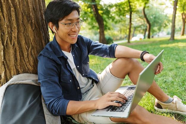 Sourire étudiant Asiatique à Lunettes à L'aide D'un Ordinateur Portable Alors Qu'il était Assis Près De L'arbre Dans Le Parc Photo Premium