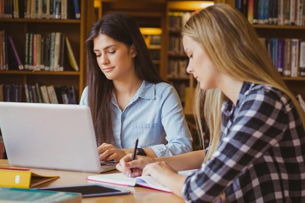 Sourire d'étudiants à l'aide d'un ordinateur portable dans la bibliothèque Photo Premium