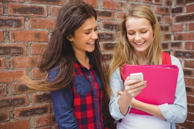 Sourire d'étudiants à l'aide d'un smartphone à l'université Photo Premium