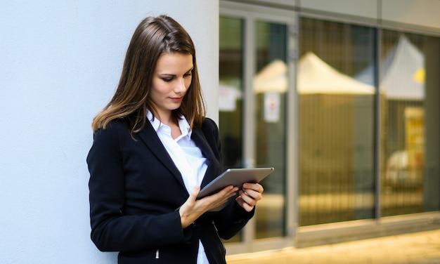 Sourire De Femme D'affaires à L'aide D'une Tablette Numérique En Plein Air Photo Premium