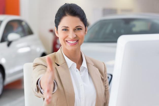Sourire de femme d'affaires atteignant la poignée de main Photo Premium