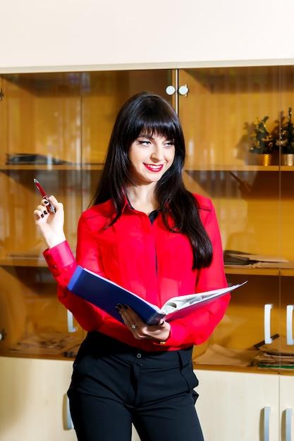 Sourire de femme d'affaires dans un chemisier rouge avec un dossier de documents au bureau Photo Premium