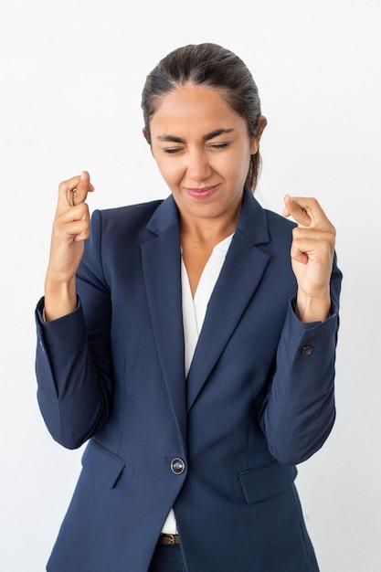 Sourire femme d'affaires avec les doigts croisés Photo gratuit