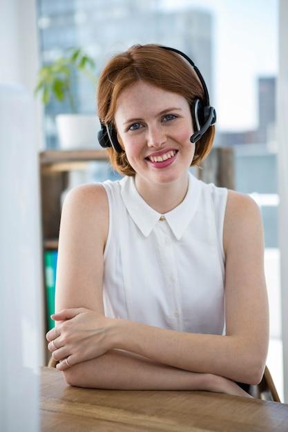 Sourire, femme d'affaires de hipster, assis à son bureau dans un casque sans fil Photo Premium