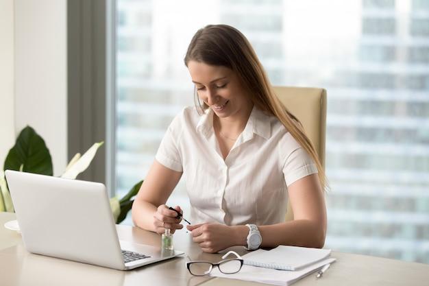 Sourire de femme d'affaires peindre des ongles au bureau Photo gratuit