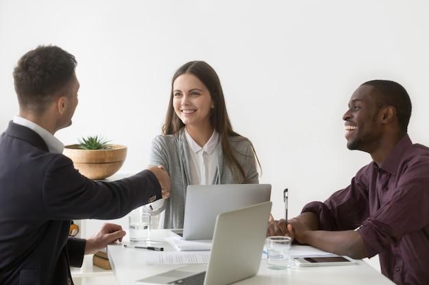 Sourire, femme affaires, serrer main, partenaire masculin, à, réunion groupe Photo gratuit