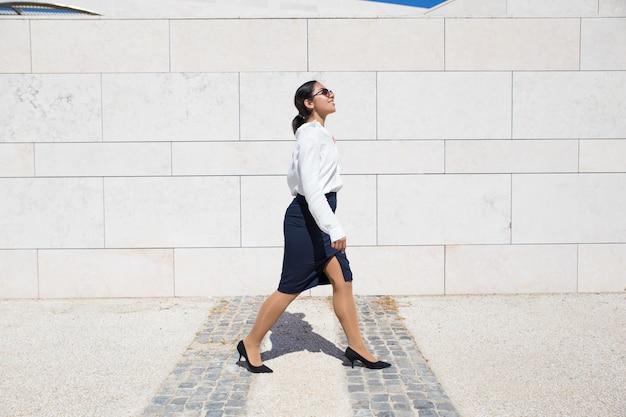 Sourire de femme d'affaires sur son chemin au bureau Photo gratuit