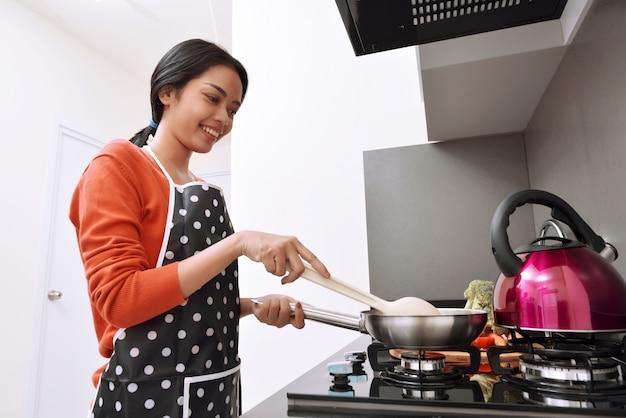 Sourire De Femme Asiatique à L'aide De La Poêle Et La Cuisson Photo Premium